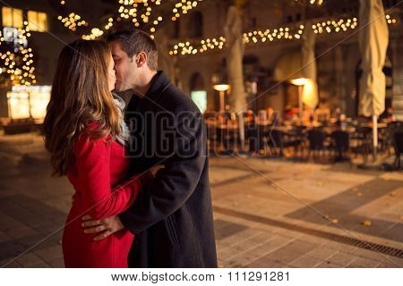 Amorous couple kissing on Christmastime, outdoor