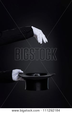 Magician's hands in white gloves with top hat over black