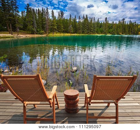 Two comfortable lounge chairs on wooden pedestal on the lake. Round lake in the coniferous forest. Canadian Rocky Mountains