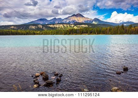 Magic lake in reserve surrounded by pine forests. Canadian Rocky Mountains, lake Annette, Jasper National Park
