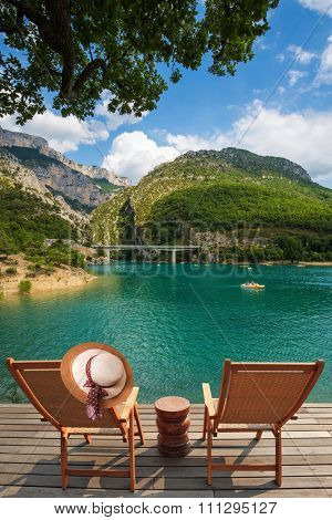 Travel to Provence. Two wooden chairs and a straw hat on the platform at lake Verdon