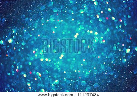 Christmas Blue Background. Glowing Holiday Abstract Defocused Background With Snowflakes and Stars. Blurred Bokeh