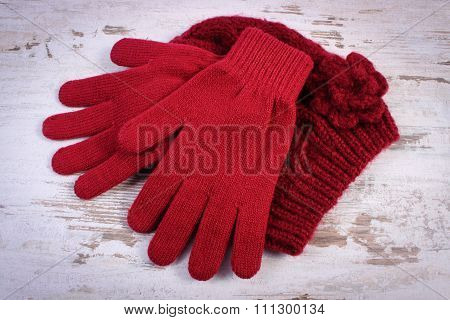 Pair Of Woolen Gloves And Cap For Woman On Old Wooden Background