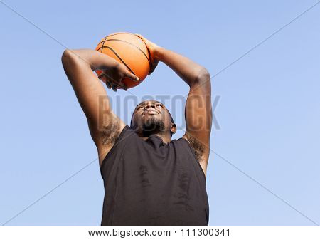 Afroamerican man street basket player against blue sky