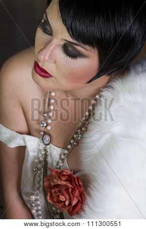 Single beautiful brunette girl 20s style flapper with jewels and white fur