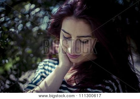 depressed melancholic girl in a forest in autumn, red long hair