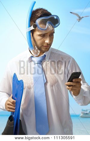 Workaholic young businessman using mobilephone on summer holiday.
