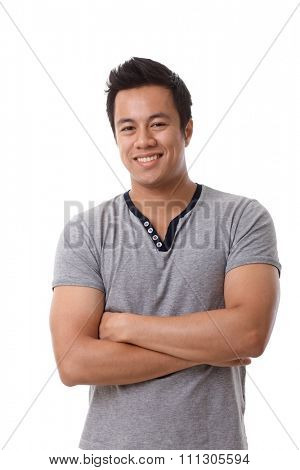 Portrait of happy young confident Asian man standing arms crossed, smiling, looking at camera.