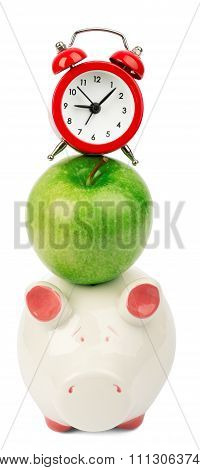 Fresh green apple with alarm clock and piggy bank