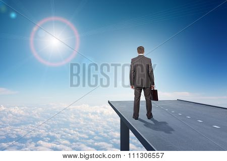 Businessman on road in sky, rear view