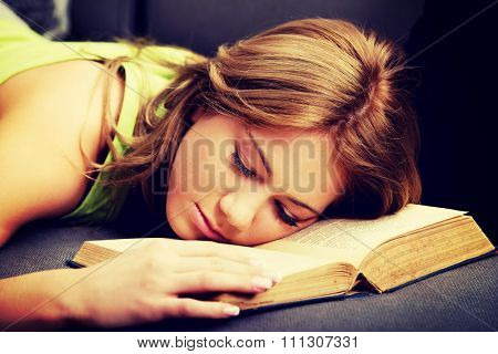 Tired and exhausted teenager with her head on book.