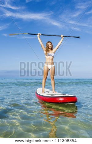 A beautiful and happy woman with arms up and learning paddle-surf