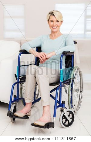 happy elderly woman sitting on wheelchair at home