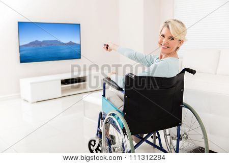 cheerful handicapped mid age woman watching tv at home