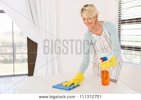 pretty senior housewife wiping table at home