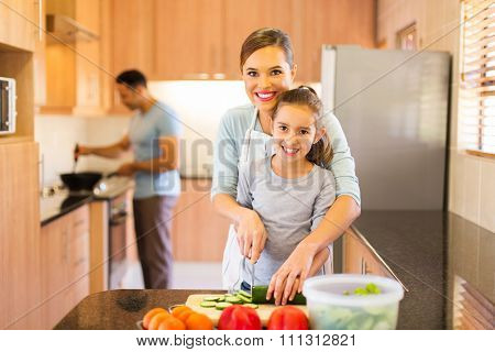 mother and daughter preparing vegetables with father cooking on background