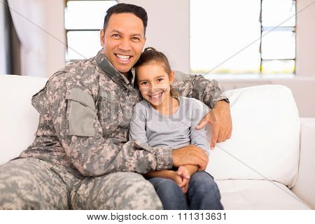 loving military father sitting on the couch with his pretty daughter