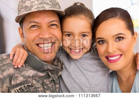 happy military family of three relaxing together at home