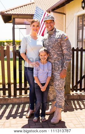 cheerful young military family standing together in front of their house
