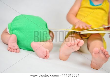 Little Girl Is Reading A Book Tog Her Baby Brother. Black And White Photo With Soft Focus On Their F