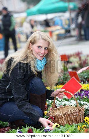 Junge, Blonde Hausfrau kauft fröhliche Blumen auf dem Markt