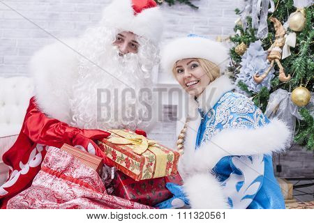 Portrait Of Santa Claus And Snow Maiden Close Up With Gift Packed In A Hand