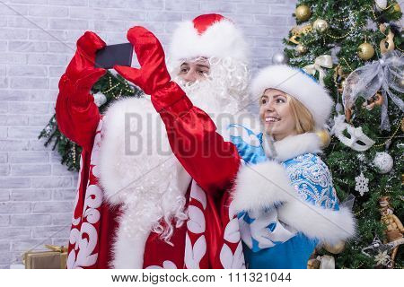 Santa Claus And Snow Maiden Making Selfie On Mobile  On Background Of Christmas Tree