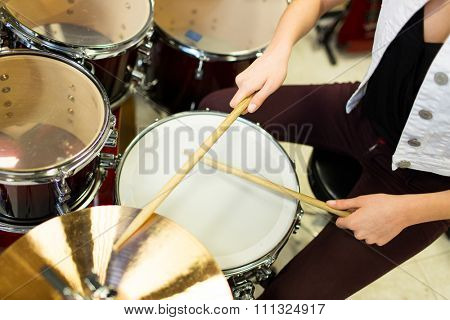 music, sale, people, musical instruments and entertainment concept - close up of female musician playing cymbals on drum kit