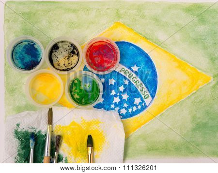 Paints Lids,brushes And And Stained Fabric On The Brazil Flag Watercolor Painting