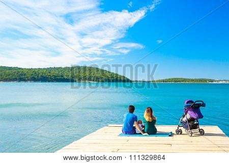 Family with Little Baby Sitting on Pier near the Sea