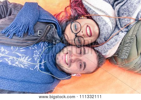 Happy couple lying down holding heads together looking up at the camera as posing for a selfie photo