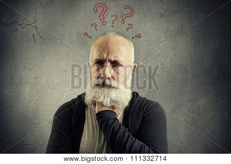 portrait of despondent senior man with red question marks above the head over grey background