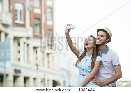 Young couple of tourists make selfie