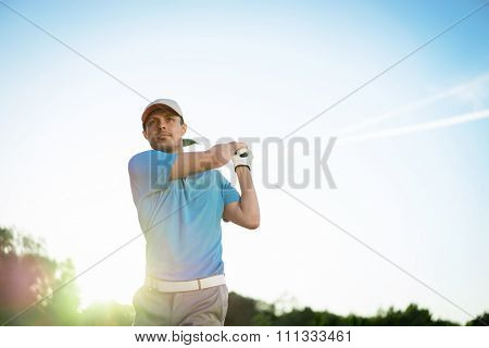 Young golfer with club outdoors