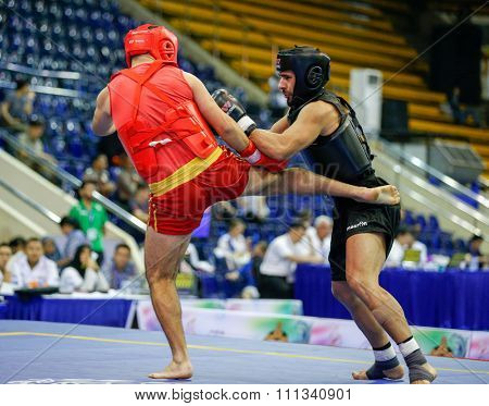 JAKARTA, INDONESIA - NOVEMBER 17, 2015: Bahzad Karam of Lebanon (red) fights Armindo Moreira of Portugal (black) in the men's 85kg Sanda event at the 13th World Wushu Championship 2015.