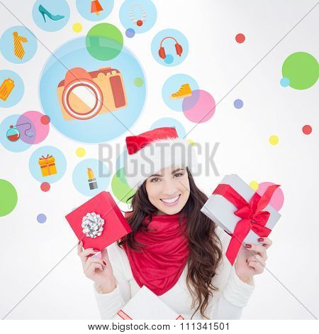 Happy brunette holding christmas gifts against dot pattern