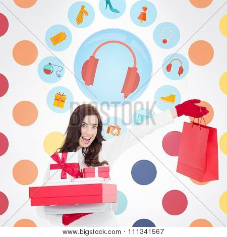Excited brunette holding gifts and showing shopping bag against colorful polka dot pattern