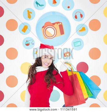 Festive brunette in winter wear holding shopping bags against colorful polka dot pattern