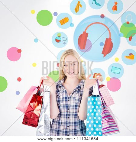 Pretty young blonde holding shopping bags against dot pattern