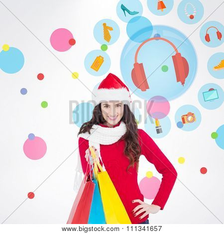 Brunette in winter clothes holding shopping bags against dot pattern