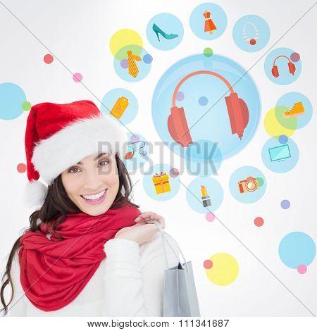 Festive brunette in winter wear holding shopping bag against dot pattern