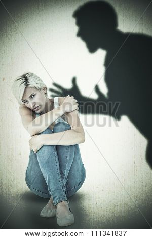 Depressed blonde looking at camera against silhouette of shouting man