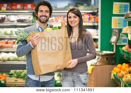 Couple holding a bag full of food at the supermarket