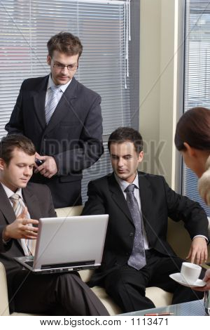 Secretary Serving Cup Of Coffee To Young Business Men In The Office