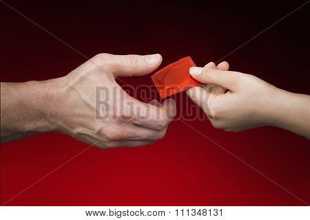 Man's Hand Giving Woman's Hand A Red  Condom