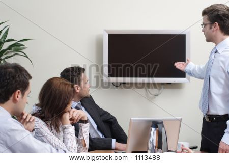 Man Making Presentation On Plasma Screen To The Group Of People