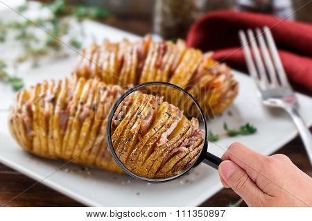 Magnifying glass examining hasselback potatoes