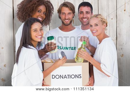 Happy volunteers putting food in donation box against wooden background