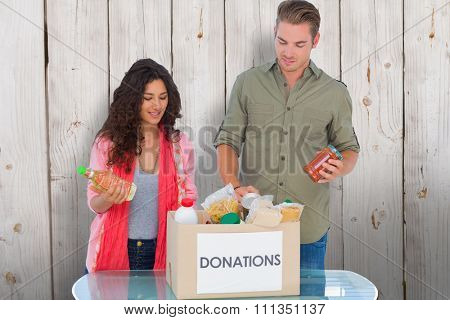 Volunteers taking out food from donations box against wooden background