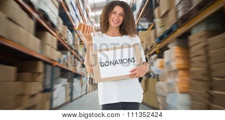 Happy volunteer holding a box of donations and jam jar against shelves with boxes in warehouse